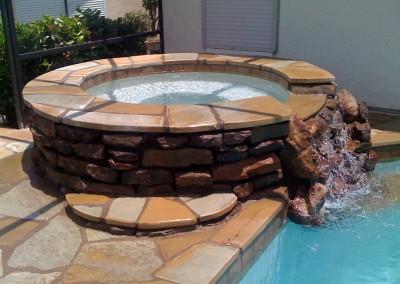 custom-natural-stone-hot-tub-runs-into-pool